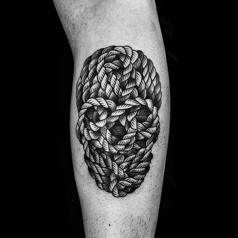 Un tatuaje que imita la silueta de una calavera, hecho con cuerda.