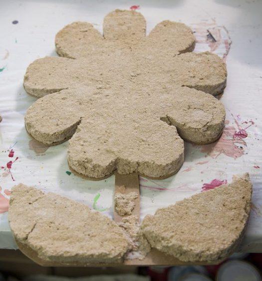 La paja de arroz se hace servir como material más ecológico para los monumentos galleros, en esta imagen se observa el proceso en forma de flor